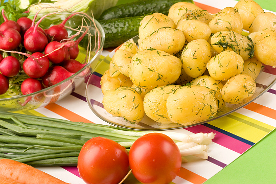 Vegetarian food: cooked potatoes, tomato, spring onions and garden radish